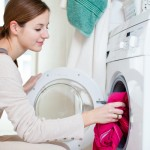 woman putting clothes in dryer | Stay at Home Mum.com.au