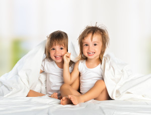 Happy Little Girl's Twin Sister In Bed Under The Blanket Having