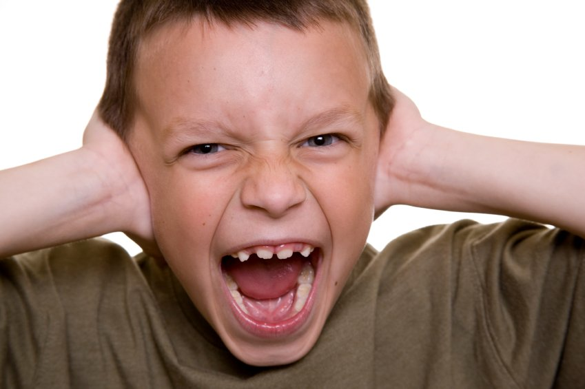 A young boy covering his ears and screaming