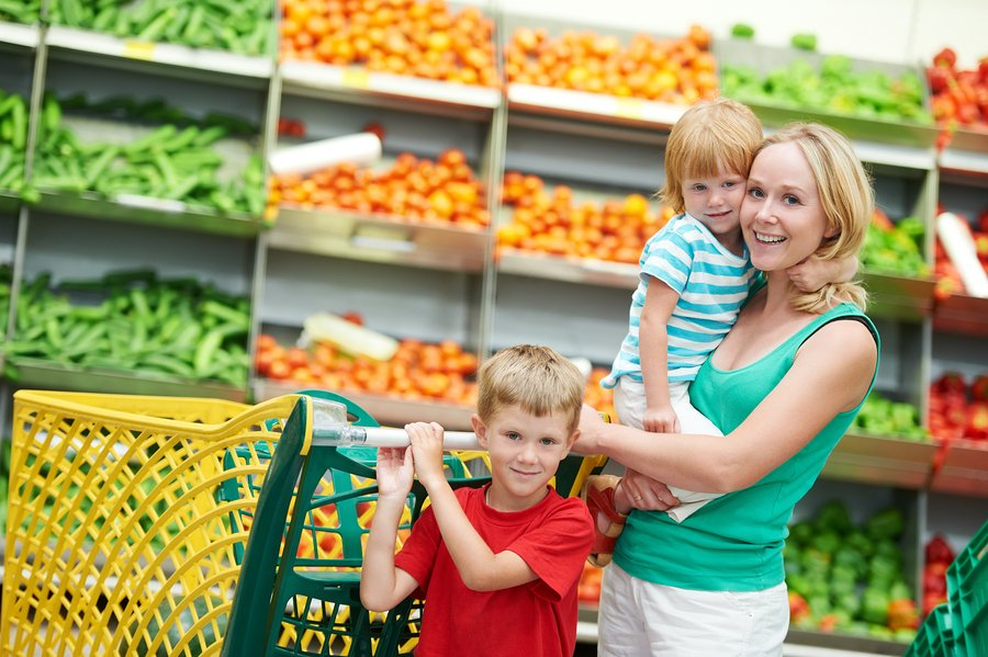 woman and child girl with shopping cart in fruit vegeable department of supermarket store