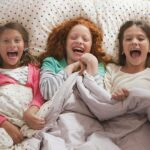 laughing girls laying in bed together jose luis pelaez inc | Stay at Home Mum.com.au