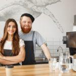 concepto de negocio de cafe positivo joven hombre barbudo y hermosa pareja atractiva barista pareja disfrutar trabajando juntos en la cafeteria moderna 1258 566 | Stay at Home Mum.com.au