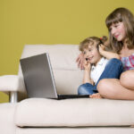 bigstock Sisters with laptop on sofa 16359140 | Stay at Home Mum.com.au